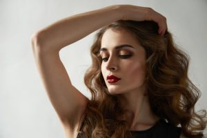 Portrait of young beautiful perfect sexy woman with long smooth hair well-groomed, fashionable styling hair, evening make-up organic cosmetics, facial features in a beauty salon