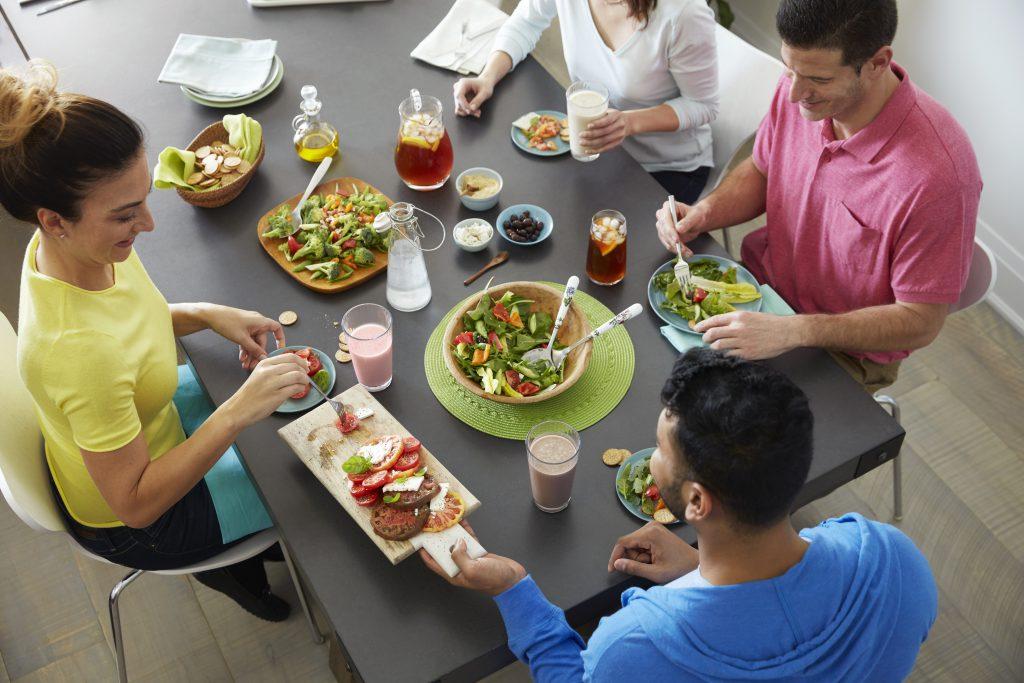 Stół ze zdrowymi warzywnymi przekąskami, wokół siedzą młodzi ludzie