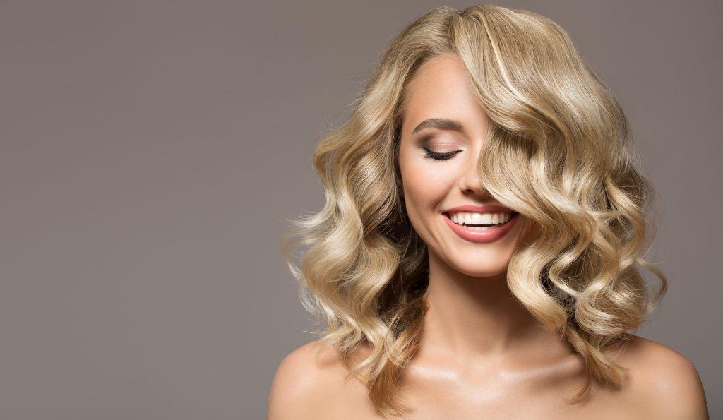 Blondynka z pięknymi kręconymi włosami uśmiecha się