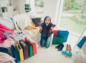 Młoda koboeta klęczy w pokoju otoczona butam, ciuchami i torbami zakupowymi