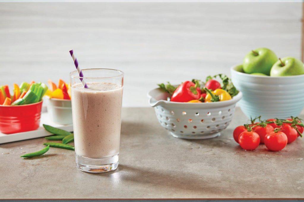 Pożywny koktajl i kolorowe, soczyste warzywa i owoce na stole.