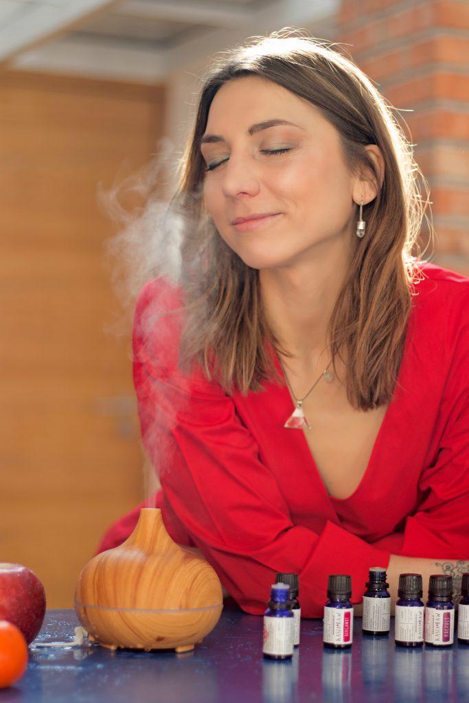 Kobieta w czerwonej bluzce wącha zapachy olejków unoszące się z aromatycznego kominka.