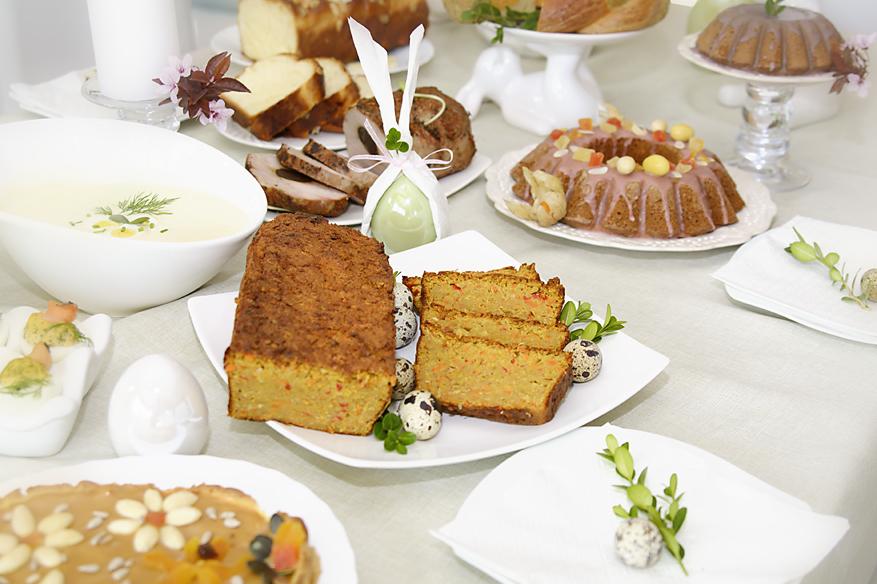 Stół z potrawami wielkanocnymi, pasztetem, babką, mazurkiem na białych talerzach.