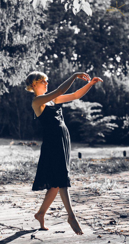 Młoda kobieta w czarnej krótkiej sukience tańczy