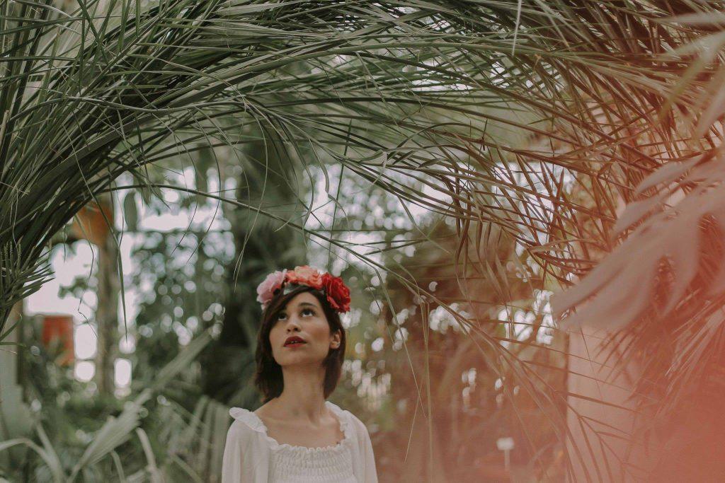 Młoda kobieta w wianku na głowie i białej bluzce pod palmami