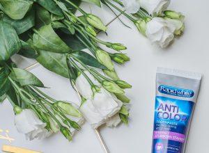 Rapid White Anti Color_Pasta do zębów na stole z kwiatami, łyżeczką i kubkiem kawy