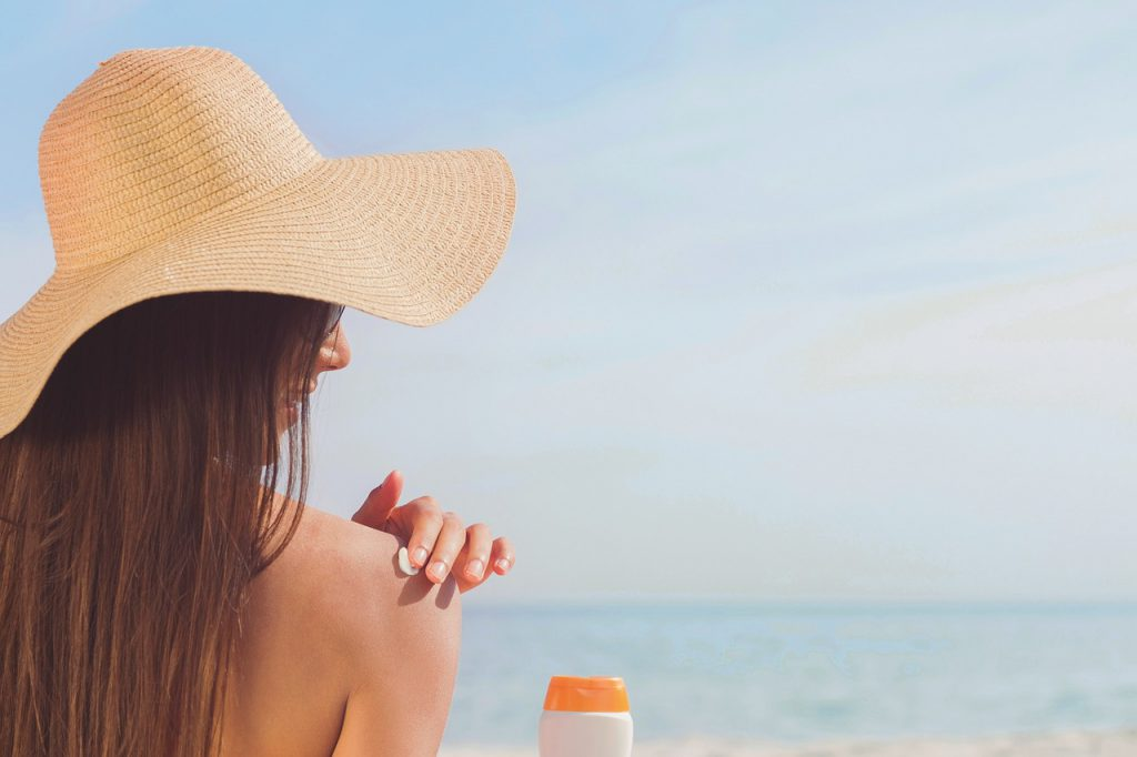 Kobieta w kapeluszu smaruje ciało mleczkiem do opalania