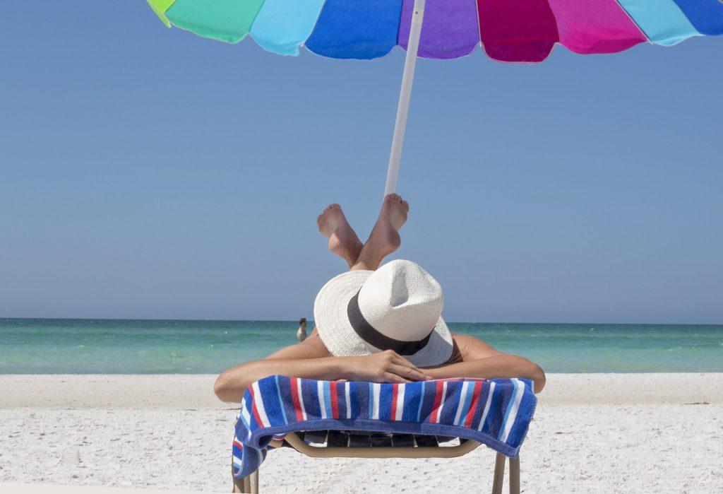 Kobieta w kapeluszu opala się na leżaku nad morzem