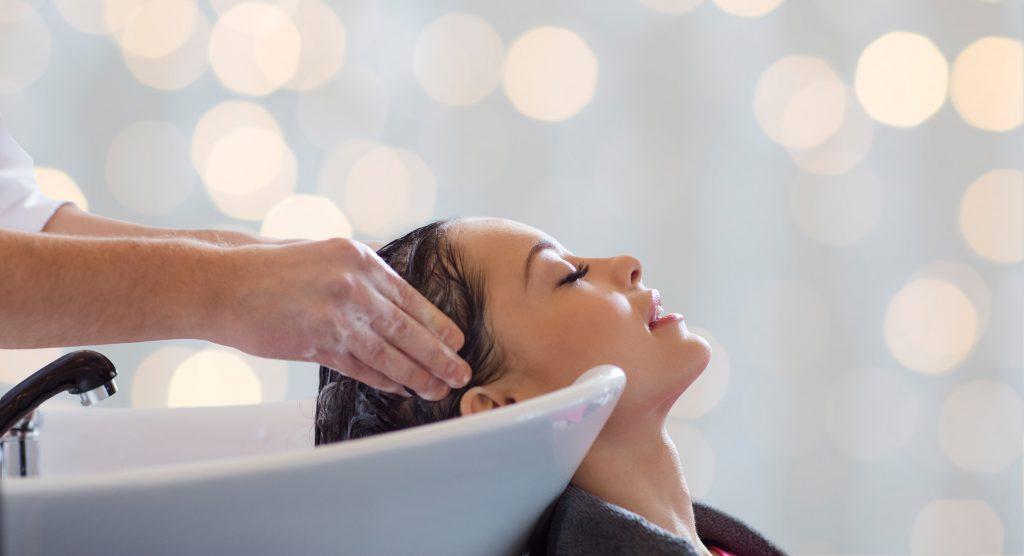 młoda kobieta podczas zabiegu mycia włosów u fryzjera